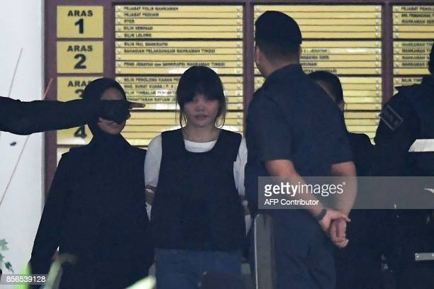 Royal Malaysian Police escort Vietnamese defendant Doan Thi Huong after her trial at the Shah Alam High Court in Shah Alam outside Kuala Lumpur on...