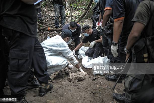 A Royal Malaysian Police forensic team handles exhumed human remains in a jungle at Bukit Wang Burma in the Malaysian northern state of Perlis which...