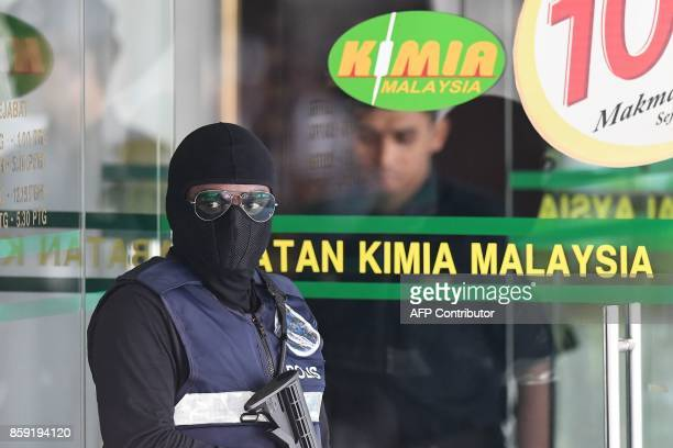 A Royal Malaysian Police officer stands guard at the main entrance of the Malaysian Chemistry Department following the arrival of accused Indonesian...