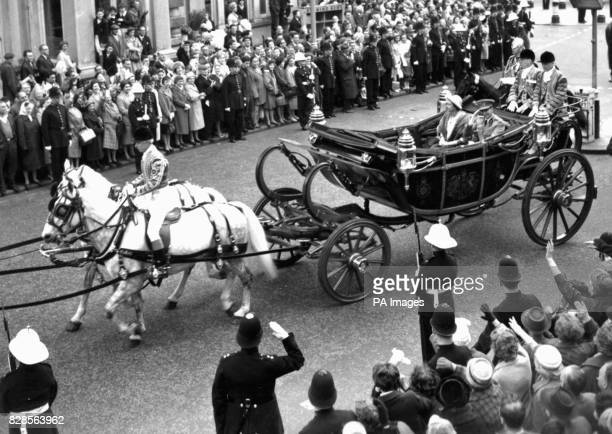A Royal Marines streetliner smartly presents arms as the Queen and King Baudouin of the Belgians drive out from Victoria Station in an open coach at...