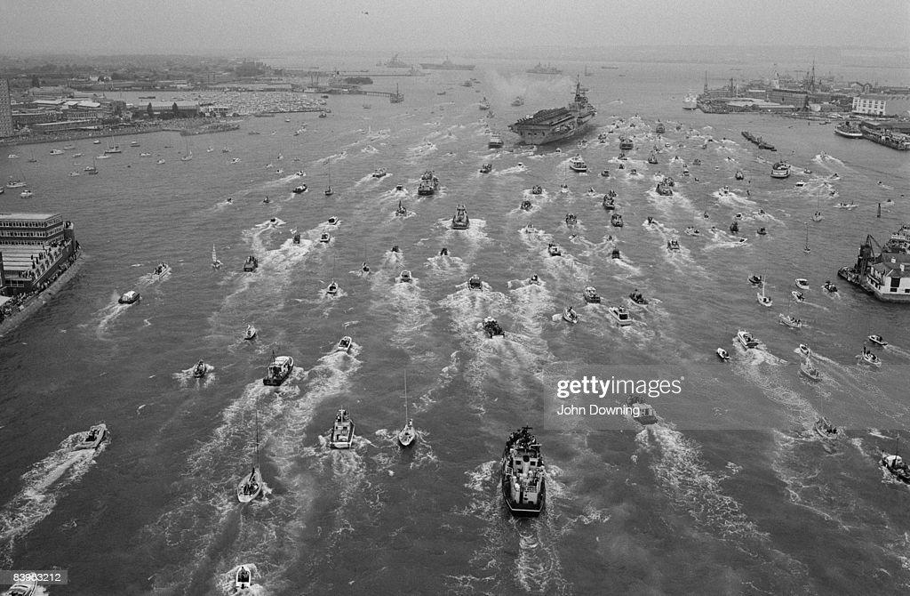 A Royal Navy aircraft carrier possibly HMS Hermes is met by a flotilla of small vessels on its return to Portsmouth from the south Atlantic after the...
