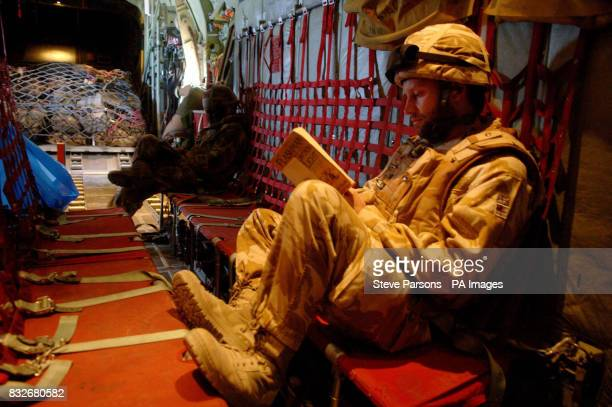 Royal Navy Officer Lt Matthew Voigt RN from Banbury reads a book while travelling on a Hercules C130 plane en route to Kandahar Afghanistan