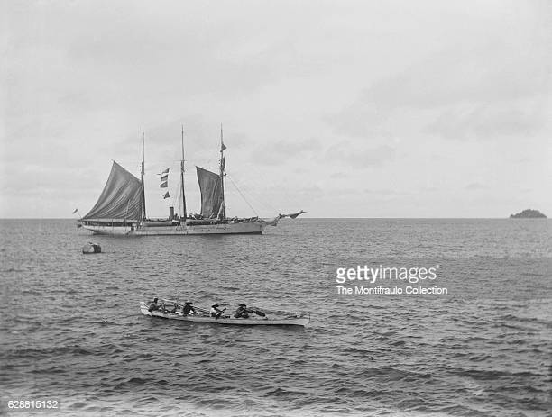 Royal Navy ship HMS Waterwitch anchored of Asian coast as a group of Asian men in a boat paddle pass HMS Waterwitch Built in 1878 as a private vessel...