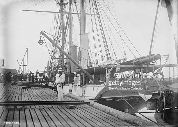 Royal Navy ship HMS Waterwitch anchored of Labuan Asian coast as a group of chinese convicts load sacks of coal HMS Waterwitch Built in 1878 as a...
