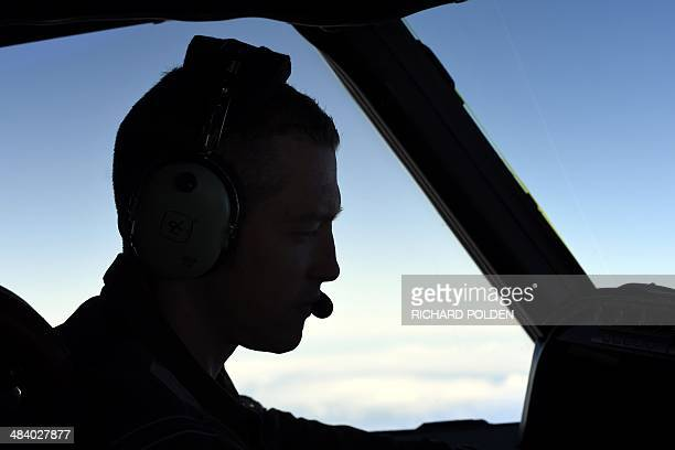 Royal New Zealand Air Force Captain Flight Lieutenant Timothy McAlevey sits in the cockpit aboard a P3 Orion maritime search aircraft as it flies...