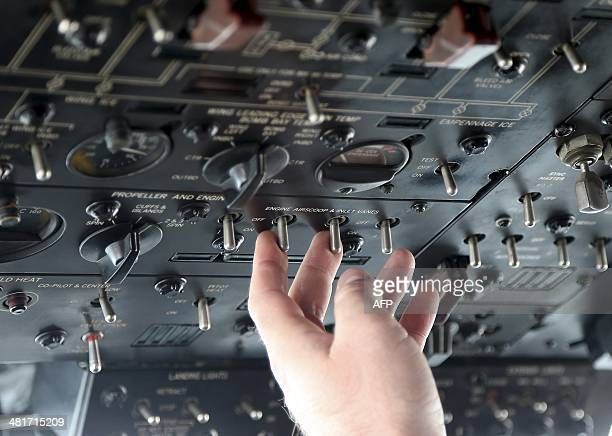 Royal New Zealand Air Force flight SGT Chris Poole on board a P3 Orion flicks switches on an instrument panel in the cockpit during an operation to...