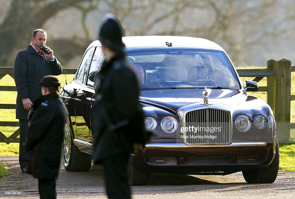 A Royal protection officer radios colleagues to request a replacement vehicle after Joe Last, Queen Elizabeth II's chauffeur, had trouble starting Queen Elizabeth II's Bentley car, as she leaves St. Mary Magdalene Church, Sandringham after attending Sunday service along with Prince Philip, Duke of Edinburgh and Lady Helen Taylor on January 13, 2012 near King's Lynn, England.