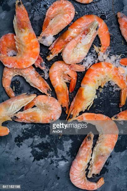 Royal shrimps with crushed ice on stone background