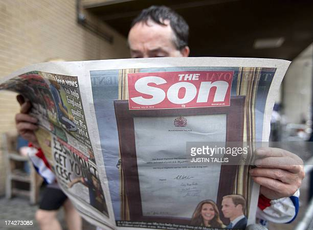 A royal supporter reads a copy of The Sun national newspaper today renamed 'The Son' announcing the birth of a royal baby boy outside St Mary's...