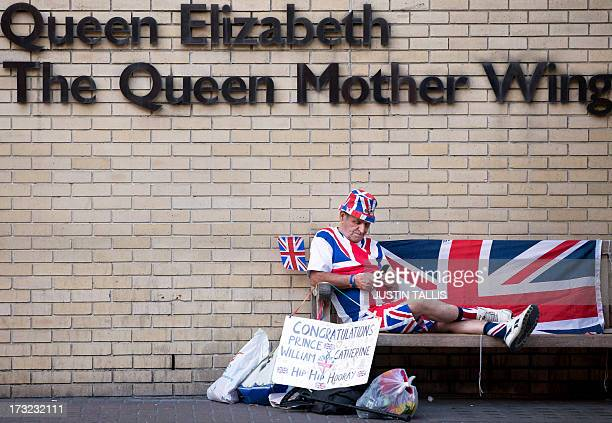 Royal supporter Terry Hutt sits on a bench looking at his mobile phone in front of the Queen Elizabeth The Queen Mother Wing directly opposite The...