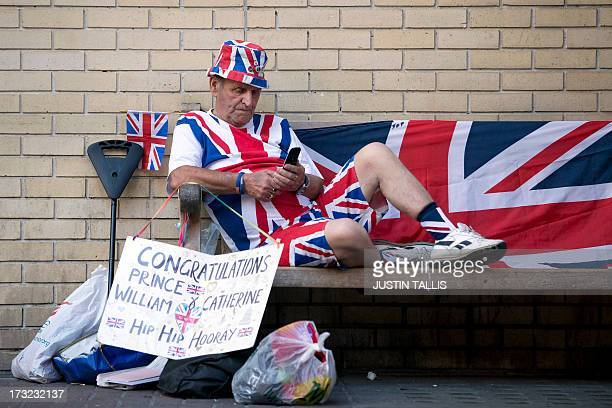 Royal supporter Terry Hutt sits on a bench looking at his mobile phone outside The Lindo Wing of Saint Mary's Hospital in London on July 10 2013...