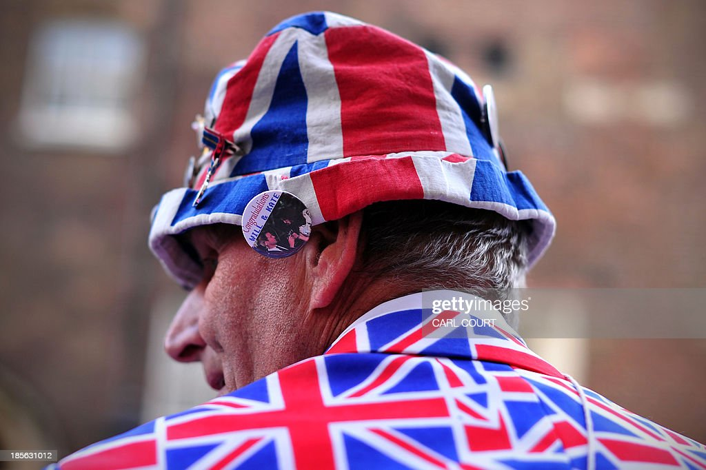 A royal supporter wears a 'Will and Kate' pin on his Union Flag hat as he waits opposite St James's Palace in central London on October 23, 2013, where Prince George of Cambridge will be baptised later in the day inside Chapel Royal. Prince William and his wife Catherine gather close friends and family for the christening of their baby son Prince George, in a low-key ceremony far removed from the global hype surrounding their wedding. AFP PHOTO/CARL COURT