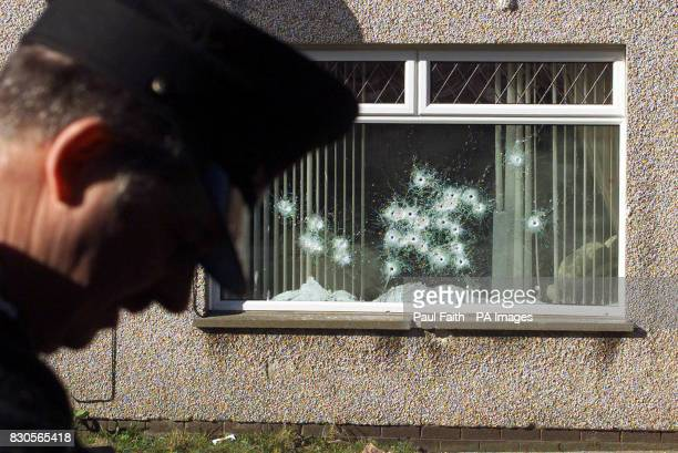 A Royal Ulster Constabulary officer looks for clues outside a house at Conlig near Bangor Co Down which was wrecked by gunfire in an apparent...