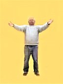 White Haired Older Man wearing a Heavy White Sweater Outstretches Two Welcoming Arms as if He is prepared to Give A Big Bear Hug to Someone - Mature Adult in Full Standing Pose against a Bright Yellow