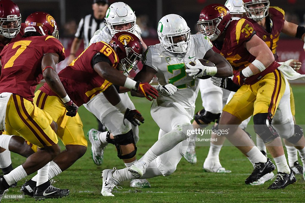 Royce Freeman #21 of the Oregon Ducks advances the ball under pressure from the USC Trojans defense at Los Angeles Memorial Coliseum on November 5, 2016 in Los Angeles, California.