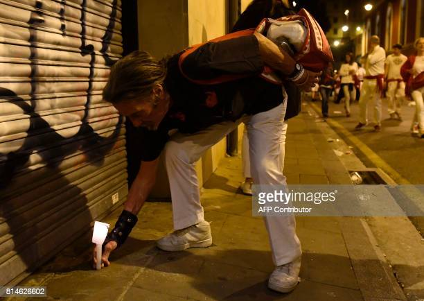 A rReveller places his candle on the ground after the singing of 'Pobre de Mi' which marks the end of the San Fermin festival in Pamplona early on...