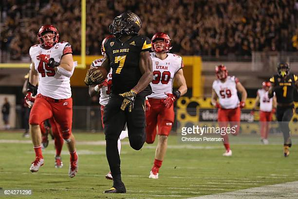 Rrunning back Kalen Ballage of the Arizona State Sun Devils runs with the football ahead of defensive back Brian Allen and defensive back Justin...