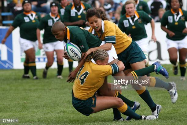 Ruan Sims and Lisa Fiaola of Team Australia tackle Zandile Nojoko of Team South Africa during their match on day one of the Women's Rugby World Cup...