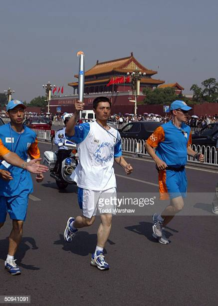 Ruan Yee carries the flame on ChangAn Avenue during Day 6 of the Athens 2004 Olympic Torch Relay on June 9 2004 in Beijing China The Olympic Flame...
