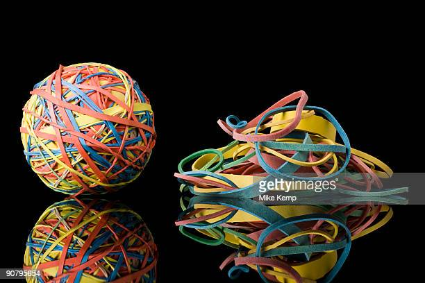 rubber band ball next to a pile of rubber bands