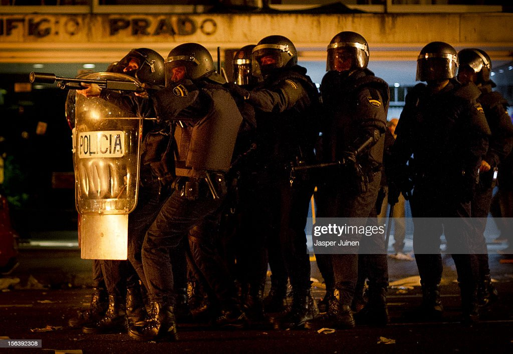 A rubber bullet leaves the barrel as a riot policeman fires at demonstrators after a demonstration near the Spanish parliament turned violent on November 14, 2012 in Madrid, Spain. A coordinated general strike by unions in Spain and Portugal has paralysed public transport in the two countries with further strikes planned across Europe. The strike against the governments' austerity measures have force hundreds of flights to be cancelled and factories and ports to come to a standstill.