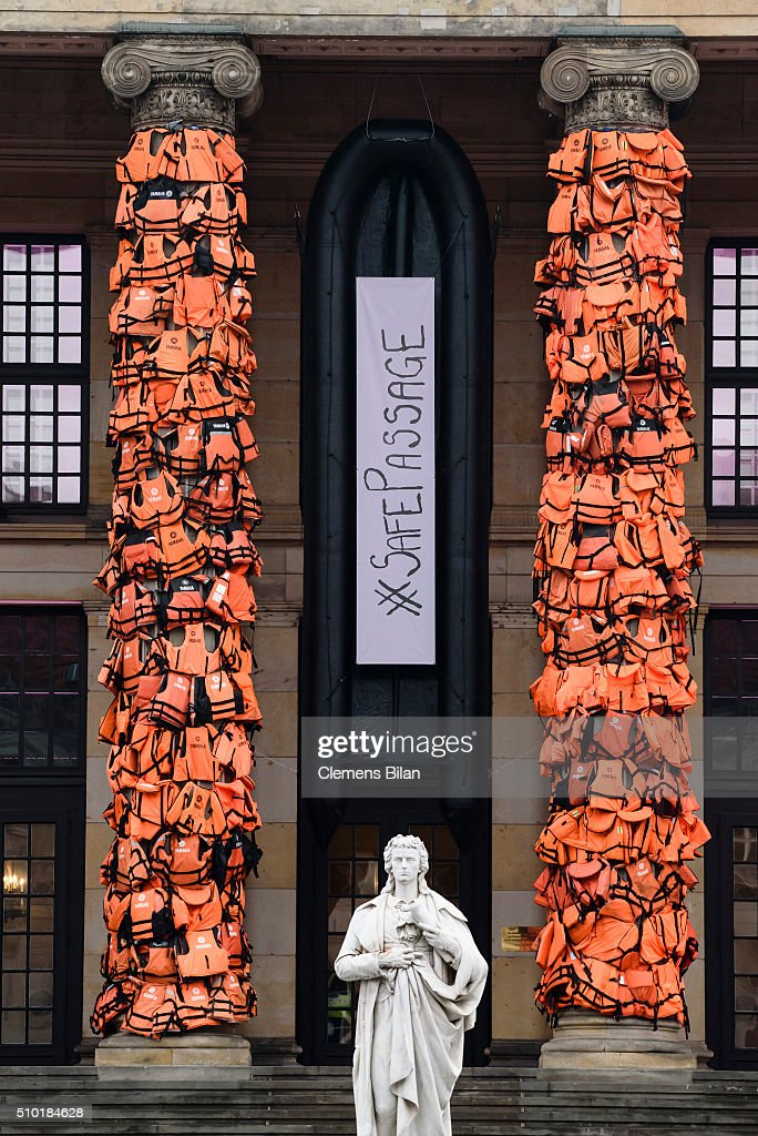 A rubber dinghy with the inscription 'Safe Passage' is shown in an art installation by Chinese artist Ai Weiwei that consists of life vests worn by refugees bound to the columns of the concert house at Gendarmenmarkt on February 14, 2016 in Berlin, Germany. The life vests were among the thousands discarded by migrants and refugees after they crossed the sea from Turkey to Greece. Ai Weiwei lives in Berlin and is currently involved in several projects relating to refugees. Up to 80,000 refugees currently live in Berlin and the city is preparing for the likely arrival of 30,000 more in 2016.