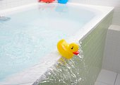 Rubber duck falling out of bath overflowing with water