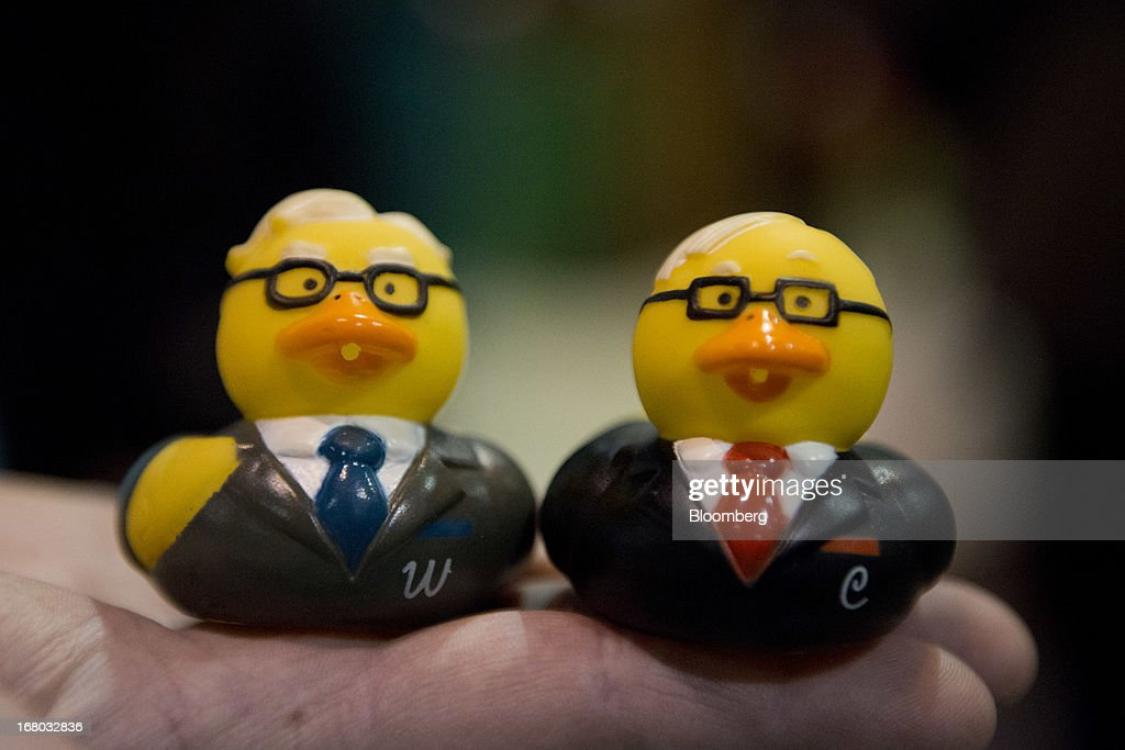 Rubber ducks made in the image of Warren Buffett, chairman and chief executive officer of Berkshire Hathaway Inc., left, and Charles Munger, vice chairman of Berkshire, are displayed for a photograph on the exhibition floor during the Berkshire shareholders meeting in Omaha, Nebraska, U.S., on Saturday, May 4, 2013. Warren Buffett's Berkshire Hathaway Inc.'s cash hoard hit a record as first-quarter profit jumped 51 percent on gains from equity-linked derivatives and insurance operations. Photographer: Daniel Acker/Bloomberg via Getty Images