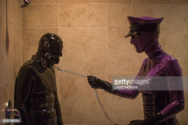 Rubber Lynn is dominated by Jenna Latex in a shower at a dungeon party during the DomCon LA domination convention on May 22 2016 in Los Angeles...