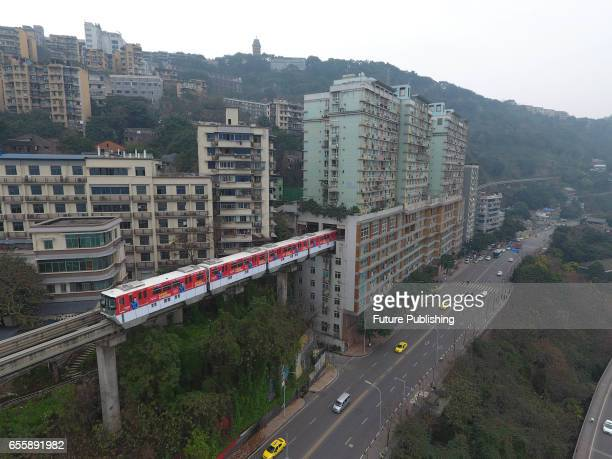 A rubberwheel lightrail train passes through a 19floor building which hosts Lizibai Station on March 18 2017 in Chongqing China The building was...
