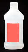 Opaque plastic jar of rubbing alcohol with blank label. Black background. Vertical.