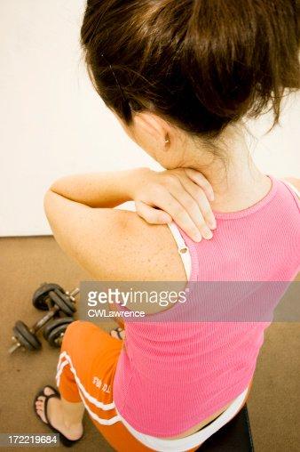 rubbing her shoulder