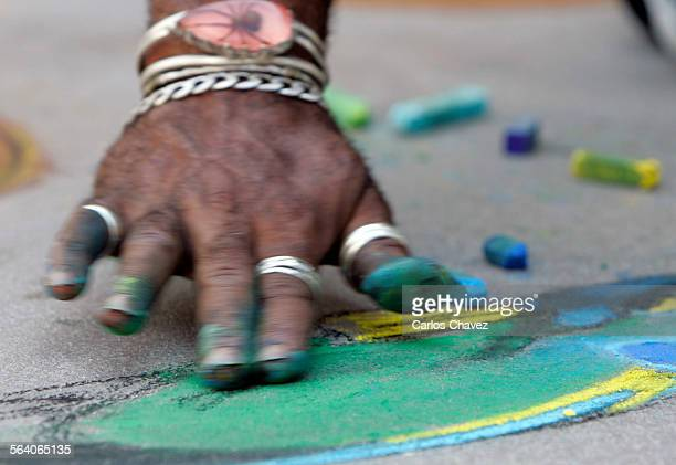 Rubbing in a bit of color is the hand of artist Randall Williams during the14th Annual Pasadena Chalk Festival where hundreds of artist used the...