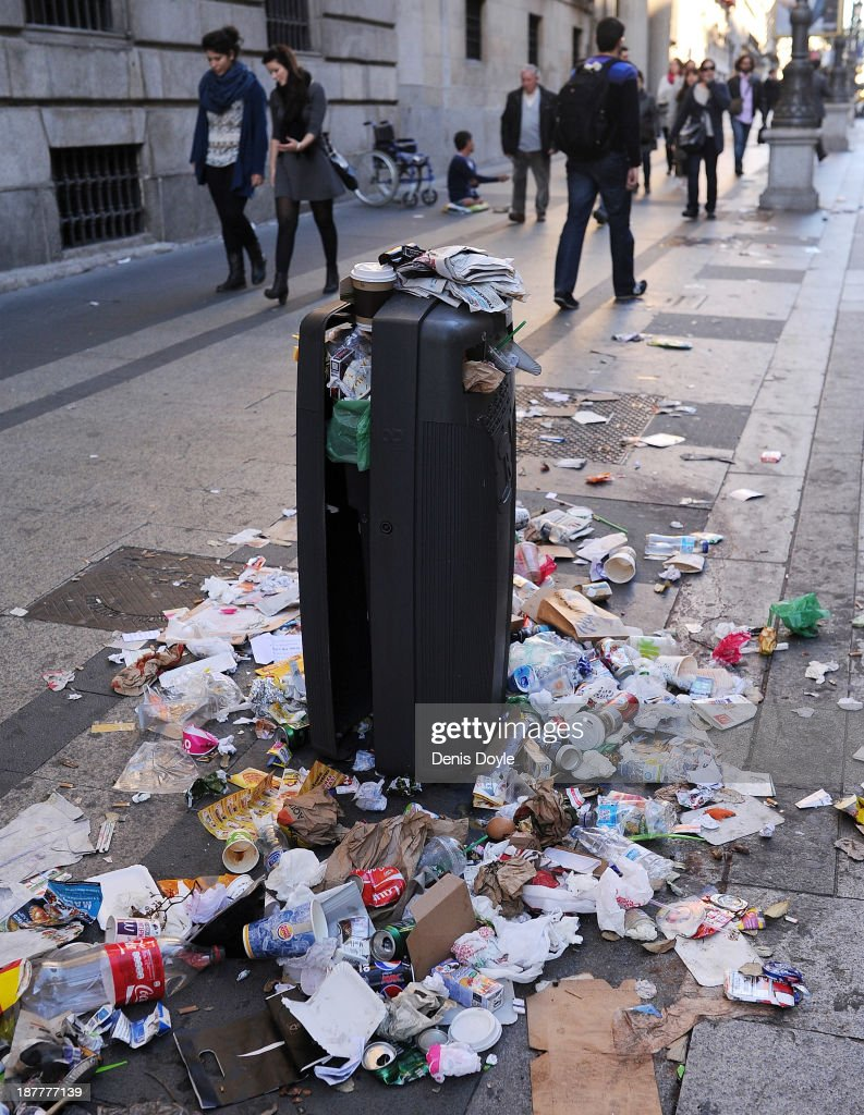 Rubbish spills onto the street from an overflowing bin in the city centre on November 12, 2013 in Madrid, Spain. Street cleaners, garbage collectors and public park gardeners working for Madrid city council started an indefinite strike six days ago after the private contracters plan to axe more than 1,000 jobs and introduce a 40% pay cut for the remaining workers.