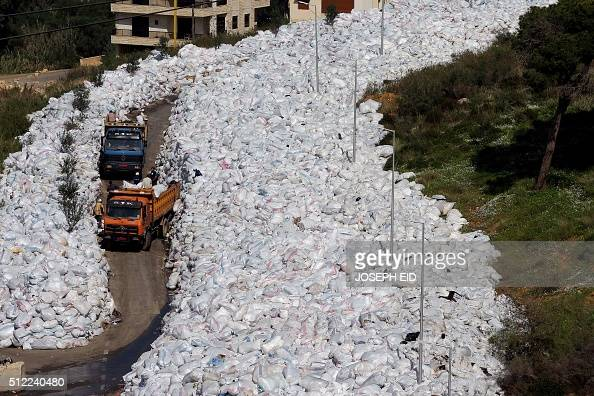 Rubbish trucks drive between a built up pile of waste on a street in Beirut's northern suburb of Jdeideh on February 25 2016 Lebanon canceled a plan...