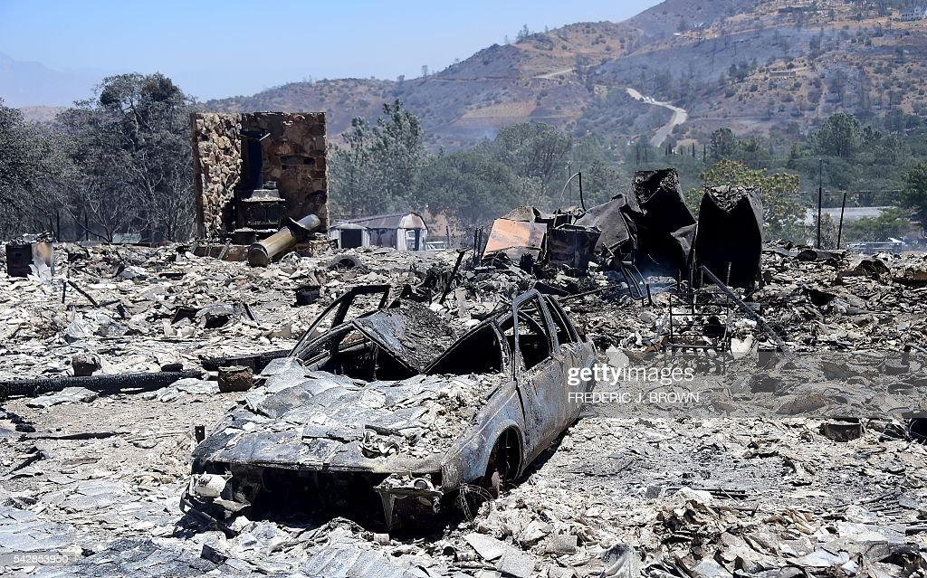 Rubble from a demolished home with vehicle out front are seen in the community of Squirrel Valley in Lake Isabella, California on June 24, 2016. An intense wildfire broke out yesterday afternoon scorched dozens of homes and structures in this mountainous community northeast of Bakersfield in Kern County. / AFP / FREDERIC
