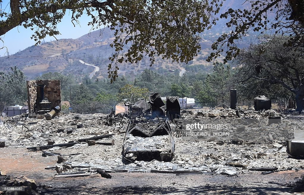 Rubble from a demolished home with vehicle out front are seen in the community of Squirrel Valley in Lake Isabella, California on June 24, 2016y. An intense wildfire broke out yesterday afternoon scorched dozens of homes and structures in this mountainous community northeast of Bakersfield in Kern County. / AFP / FREDERIC