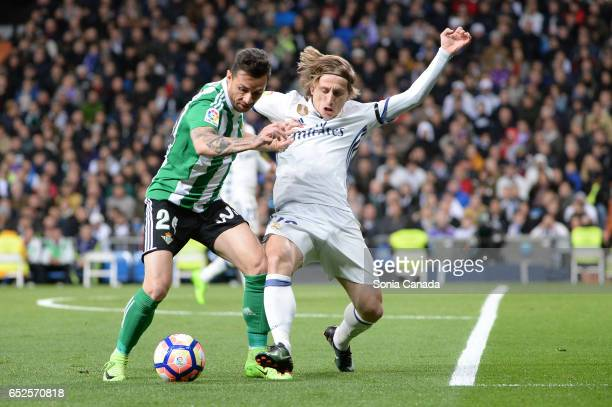 Ruben Castro #24 of Real Betis and Luka Modric #19 of Real Madrid during the La Liga match between Real Madrid CF v Real Betis Balompie at Santiago...