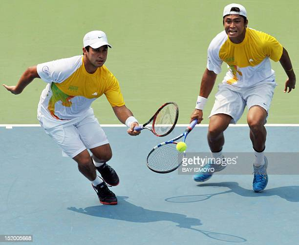 Ruben Gonzales and Treat Conrad Huey of the Philippines return a shot against Elbert Sie and Christopher Benjamin Rungkat of Indonesia during the...