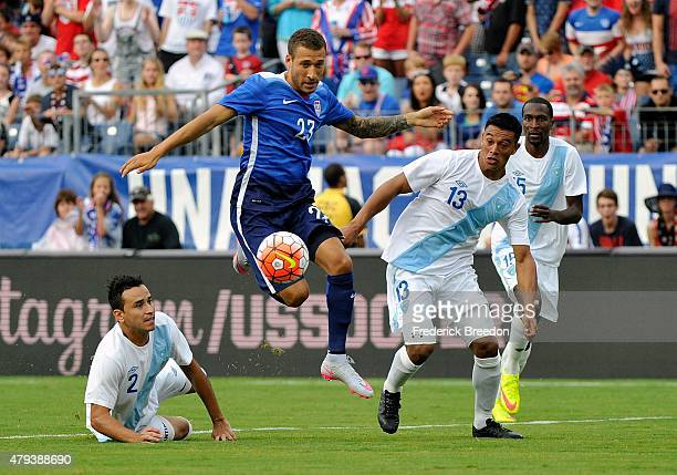 Ruben Morales and Carlos Castrillo of Guatemala watch Fabian Johnson of the United States dribble during an international friendly soccer match...