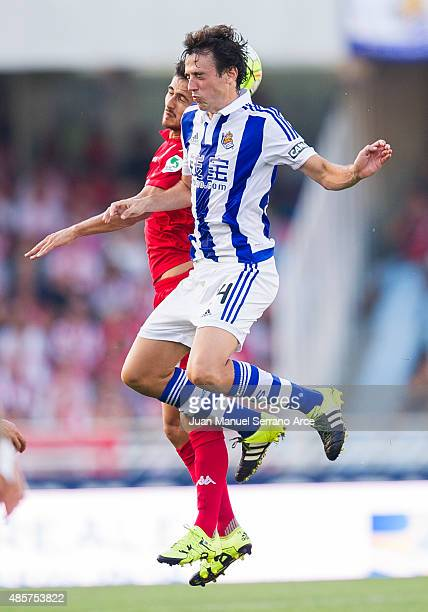 Ruben Pardo of Real Sociedad de Futbol duels for the ball with Nacho Cases of Sporting Gijon during the La Liga match between Real Sociedad de Futbol...