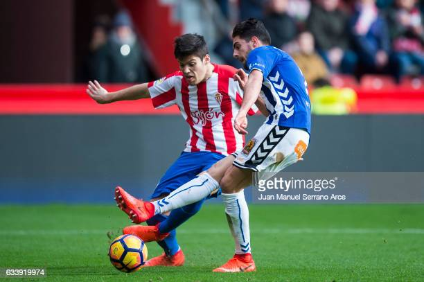Ruben Sobrino of Deportivo Alaves duels for the ball with Jorge Mere of Real Sporting de Gijon during the La Liga match between Real Sporting de...