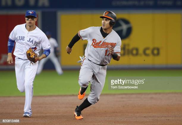 Ruben Tejada of the Baltimore Orioles advances safely from first base to third base on a double by Joey Rickard as he races toward third base in the...