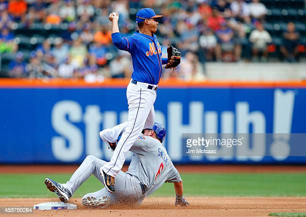 Ruben Tejada of the New York Mets attempts a third inning double play after forcing out Ryan Sweeney of the Chicago Cubs at Citi Field on August 17...