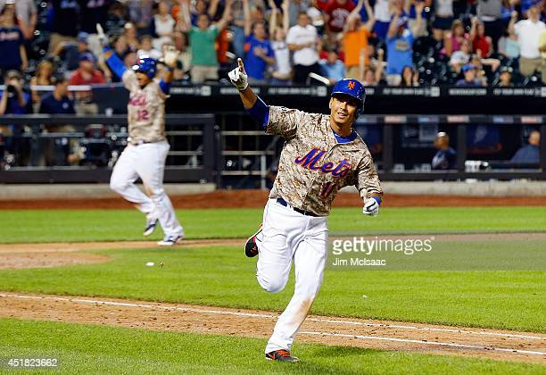 Ruben Tejada of the New York Mets celebrates his 11th inning gamewinning base hit against the Atlanta Braves as teammate Juan Lagares of the New York...
