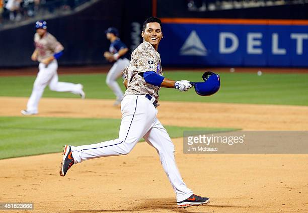 Ruben Tejada of the New York Mets celebrates his 11th inning gamewinning base hit against the Atlanta Braves at Citi Field on July 7 2014 in the...