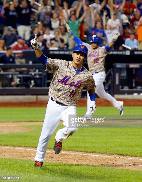Ruben Tejada of the New York Mets celebrates his 11th inning gamewinning base hit against the Atlanta Braves while running to first base as teammate...