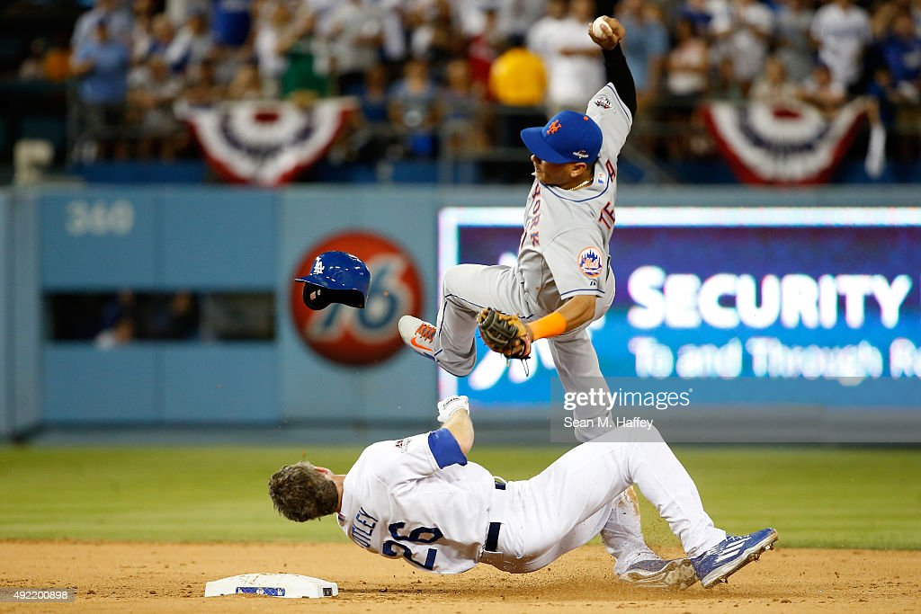 Ruben Tejada #11 of the New York Mets is hit by a slide by Chase Utley #26 of the Los Angeles Dodgers in the seventh inning in an attempt to turn a double play in game two of the National League Division Series at Dodger Stadium on October 10, 2015 in Los Angeles, California.