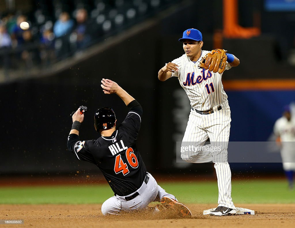 Ruben Tejada #11 of the New York Mets sends the ball to first after Koyie Hill #46 of the Miami Marlins is out at second in the fifth inning on August 13, 2013 at Citi Field in the Flushing neighborhood of the Queens borough of New York City. Brad Hand #52 of the Miami Marlins bunted the ball on the play.