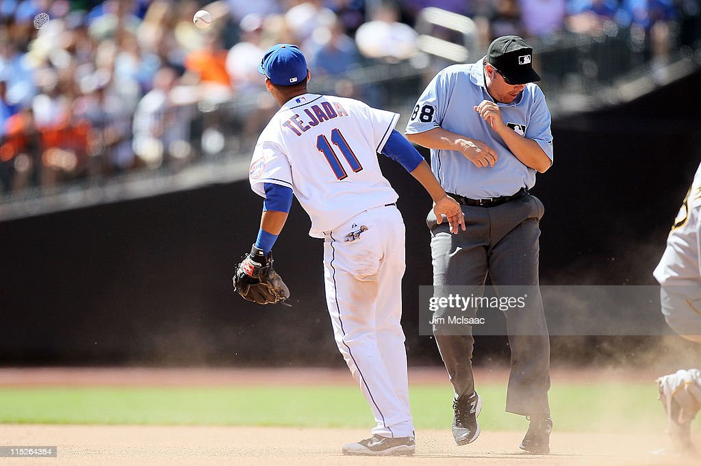 Ruben Tejada #11 of the New York Mets tries to contain anerrant throw against the Pittsburgh Pirates as umpire Doug Eddings reacts on June 2, 2011 at Citi Field in the Flushing neighborhood of the Queens borough of New York City. The Mets defeated the Pirates 9-8.